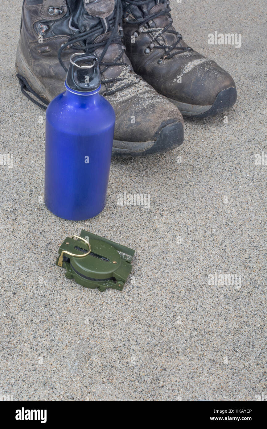 Trekking boots, blue water bottle, and compass - as metaphor for traveling and backpacking in desert or arid zones. - Stock Image