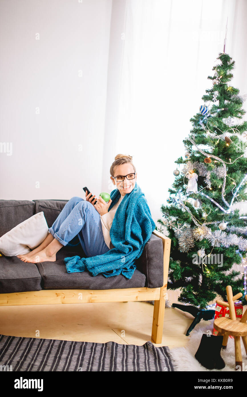 woman browsing on her smartphone, while sitting on a comfy couch - Stock Image