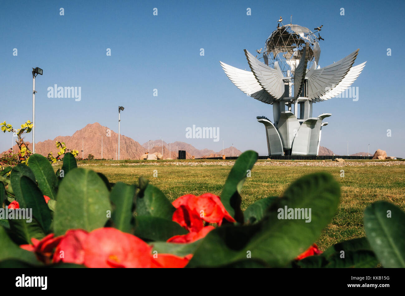Sharm el Sheikh, Sinai, Egypt - November 12, 2017: Monument Peace Square on the background of red flowers - Stock Image