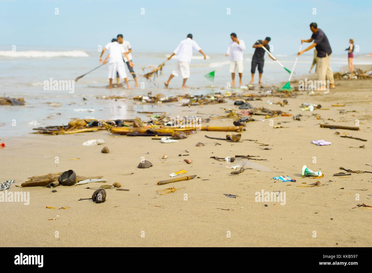 People cleaning trashy polluted with garbage ocean beach. Bali island, Indonesia - Stock Image