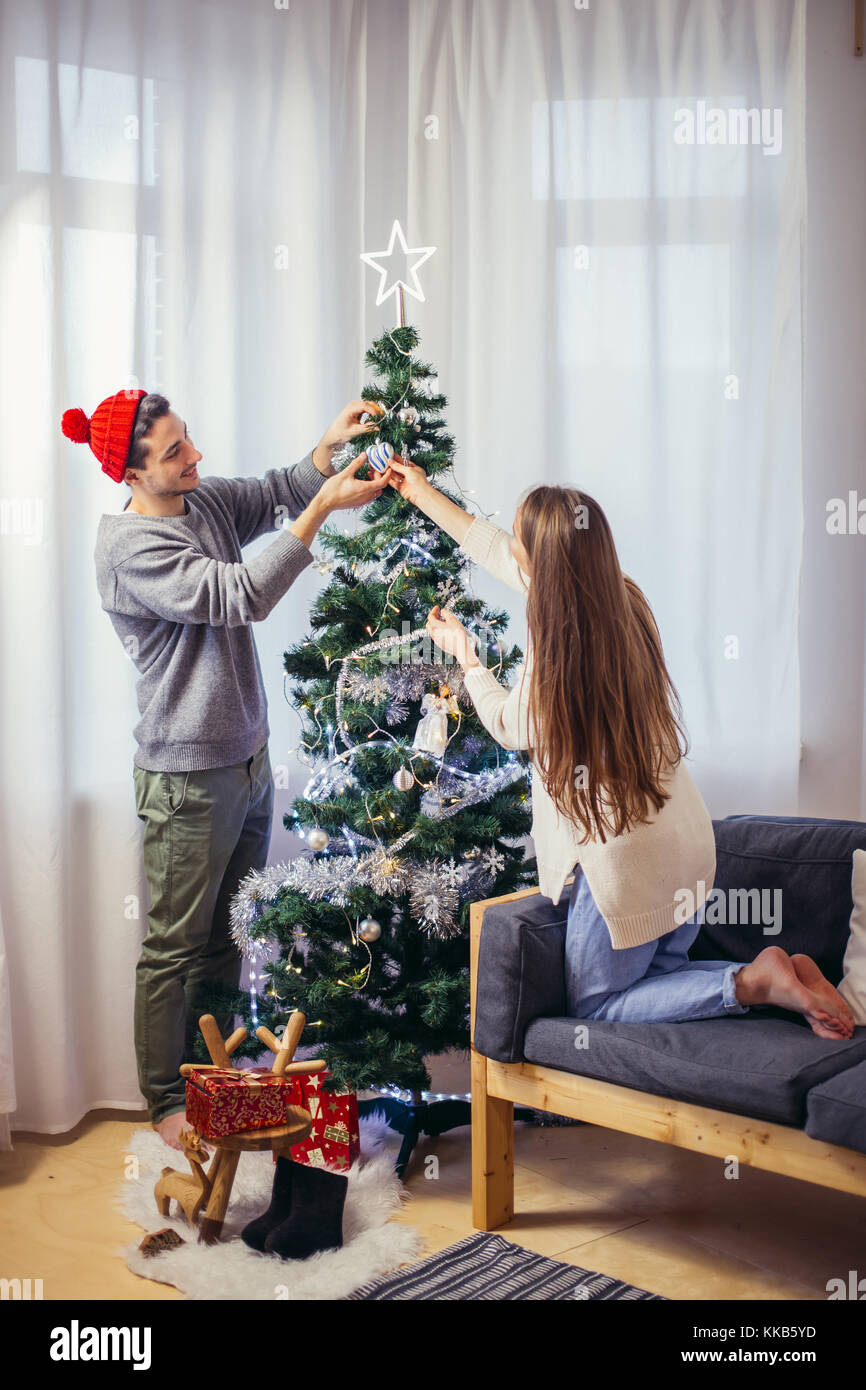 Cute, young couple decorating a Christmas tree - Stock Image