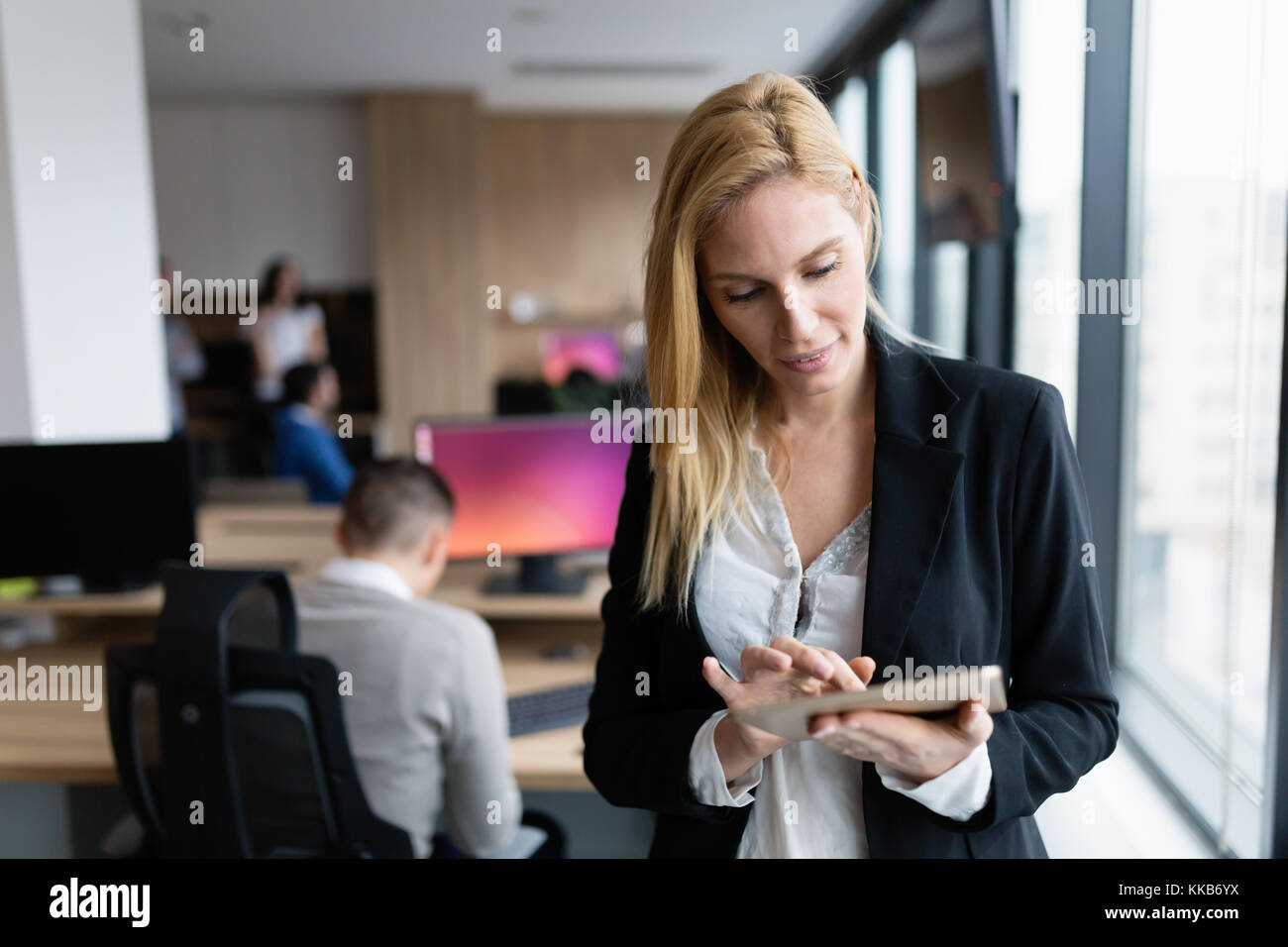 Beautiful businesswoman using digital tablet in office - Stock Image