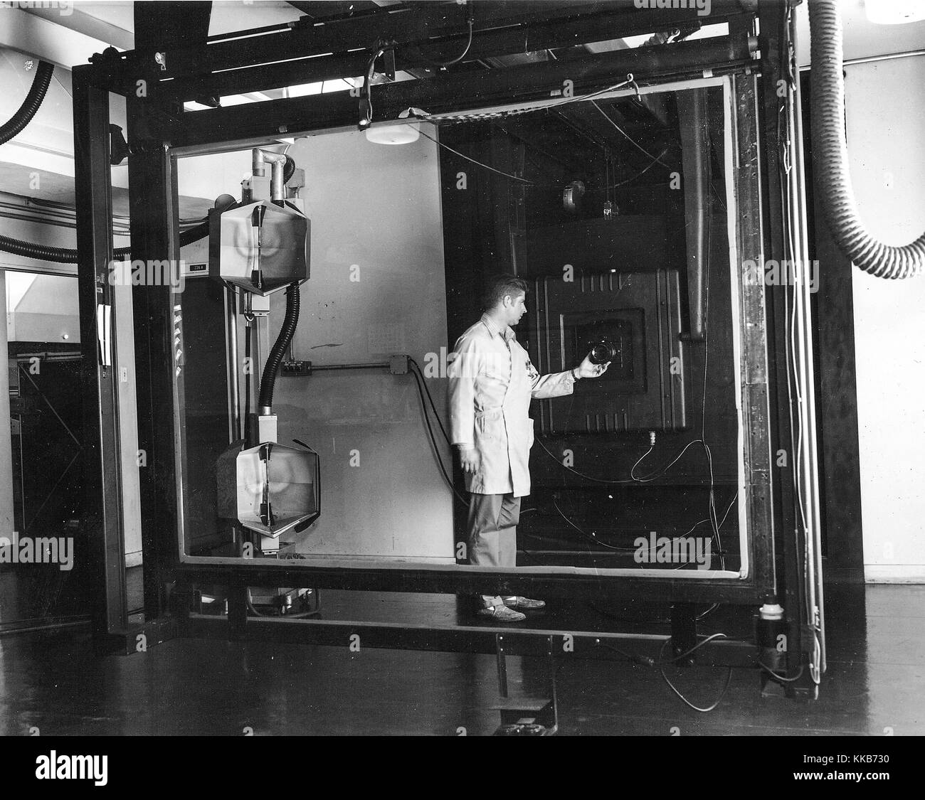 Jay Prendergast adjusts the lens on a Robertson 48-inch, 4 and a half ton camera used for precise scale transformation - Stock Image
