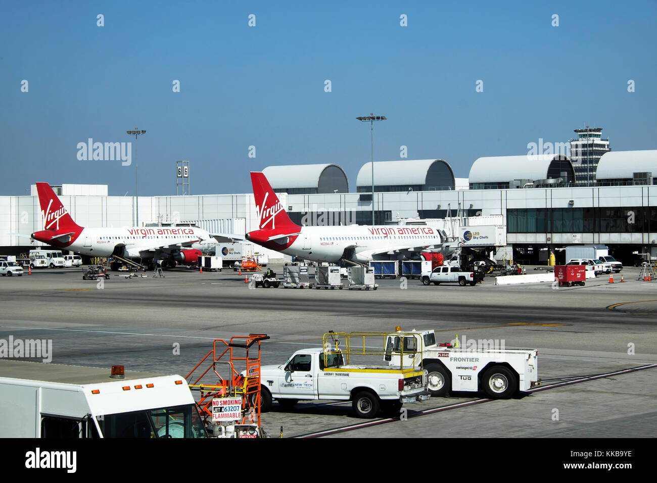 Virgin America planes on the tarmac being serviced preparing for departure at LAX airport in Los Angeles, California - Stock Image