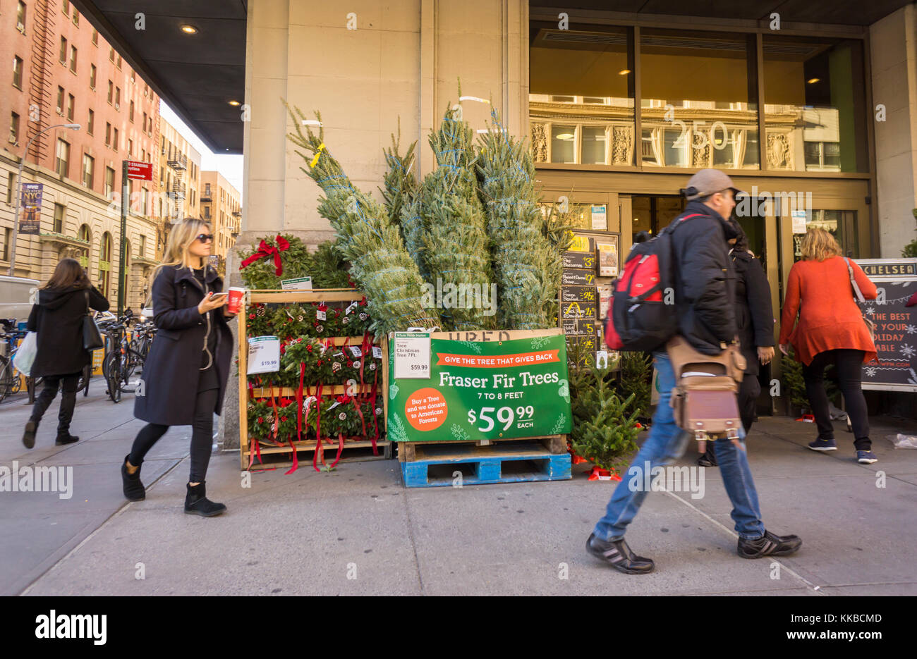 Pedestrians Pass Christmas Trees For Sale At Whole Foods Market In