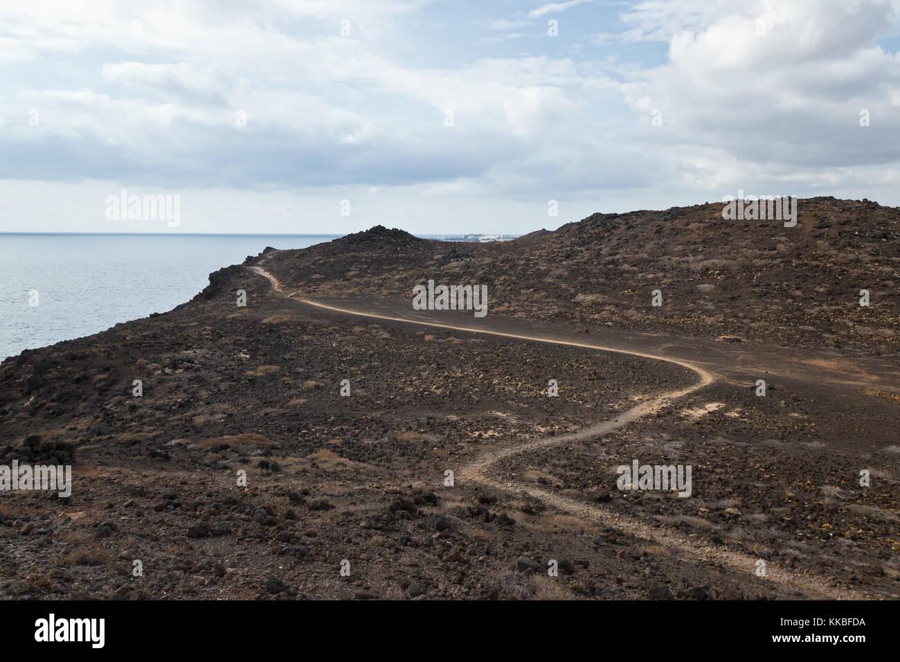 Trail in lava fields, Lanzarote, Spain - Stock Image