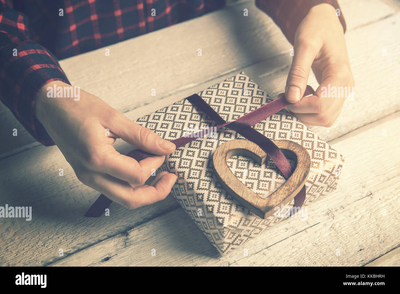 woman wrapping a gift for beloved. tying a ribbon bow with wooden heart decor - Stock Image