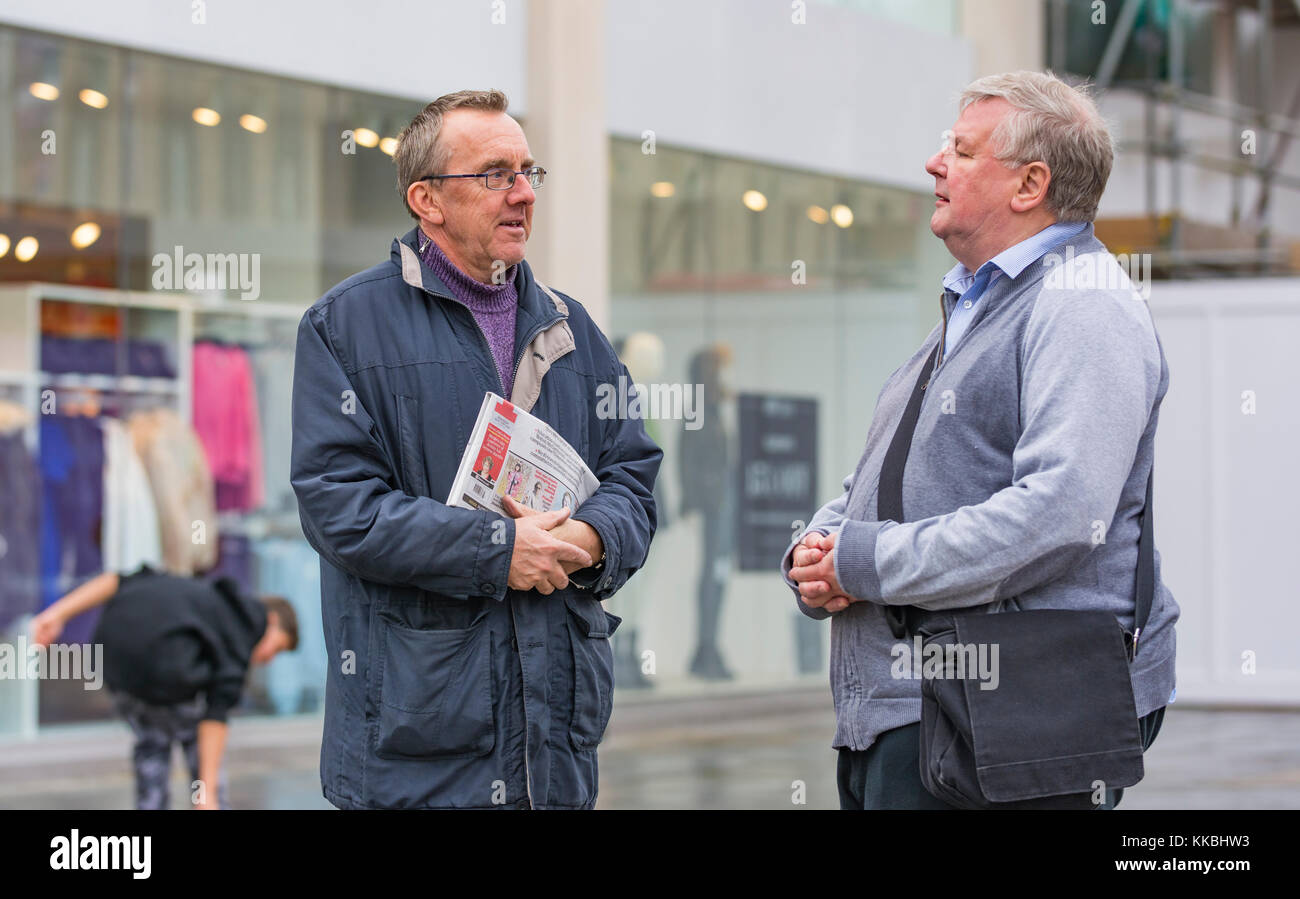 Middle aged men meet in the street and stop to chat, in the UK. - Stock Image