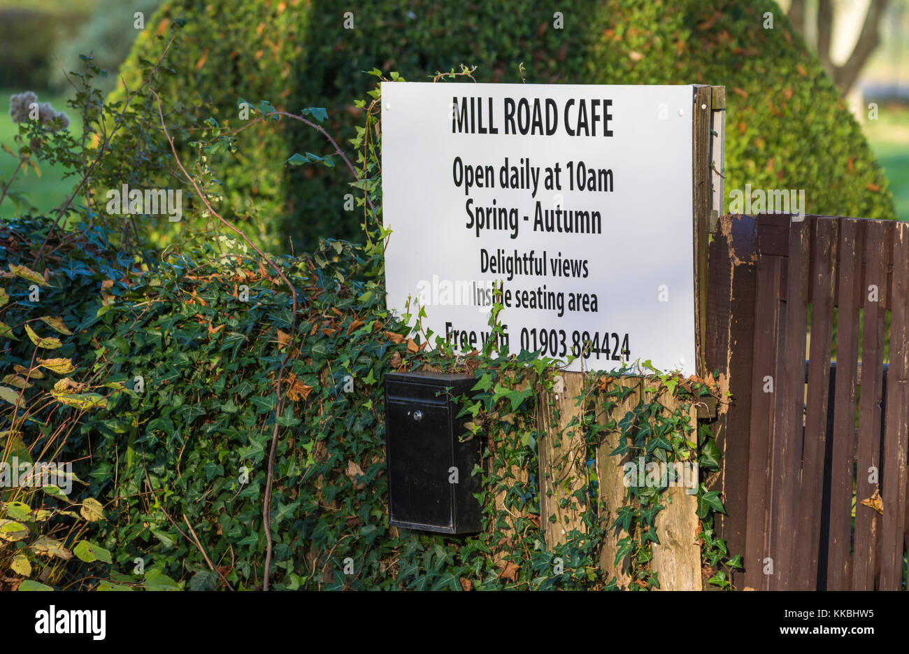 Cafe sign showing seasonal opening and closing times. - Stock Image
