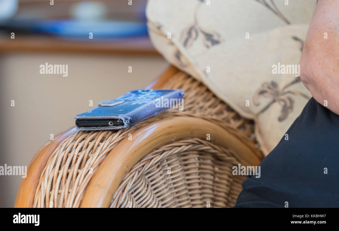 A mobile phone left on the arm of a chair not being used while in a social gathering. - Stock Image