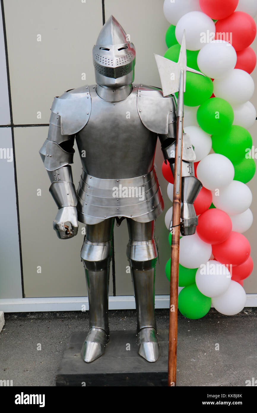 Full suit of knight armour and weapon on the street on balloon background. - Stock Image