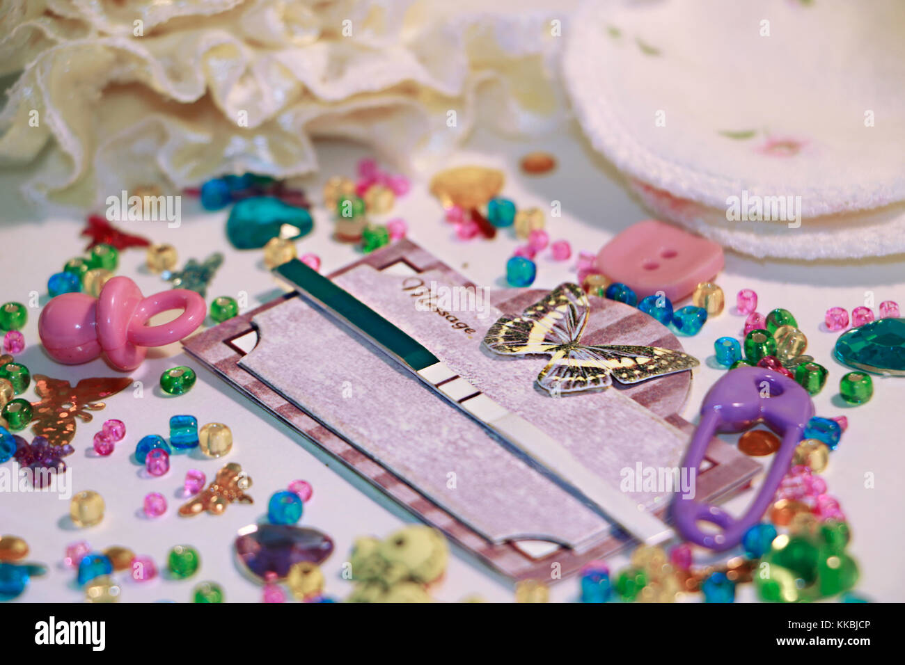 Positive pregnancy test in scrap book frame with butterfly,  cute baby accessories and spilled colored  seed beads - Stock Image