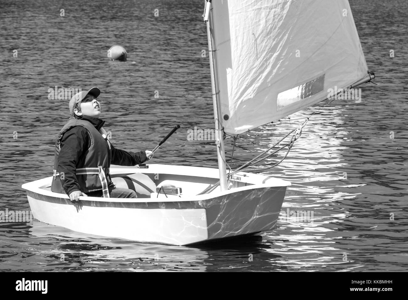 Young sailor on Optimist yacht, dinghy, looking for wind. Fordwind, boy observing the tell tales on sail. - Stock Image