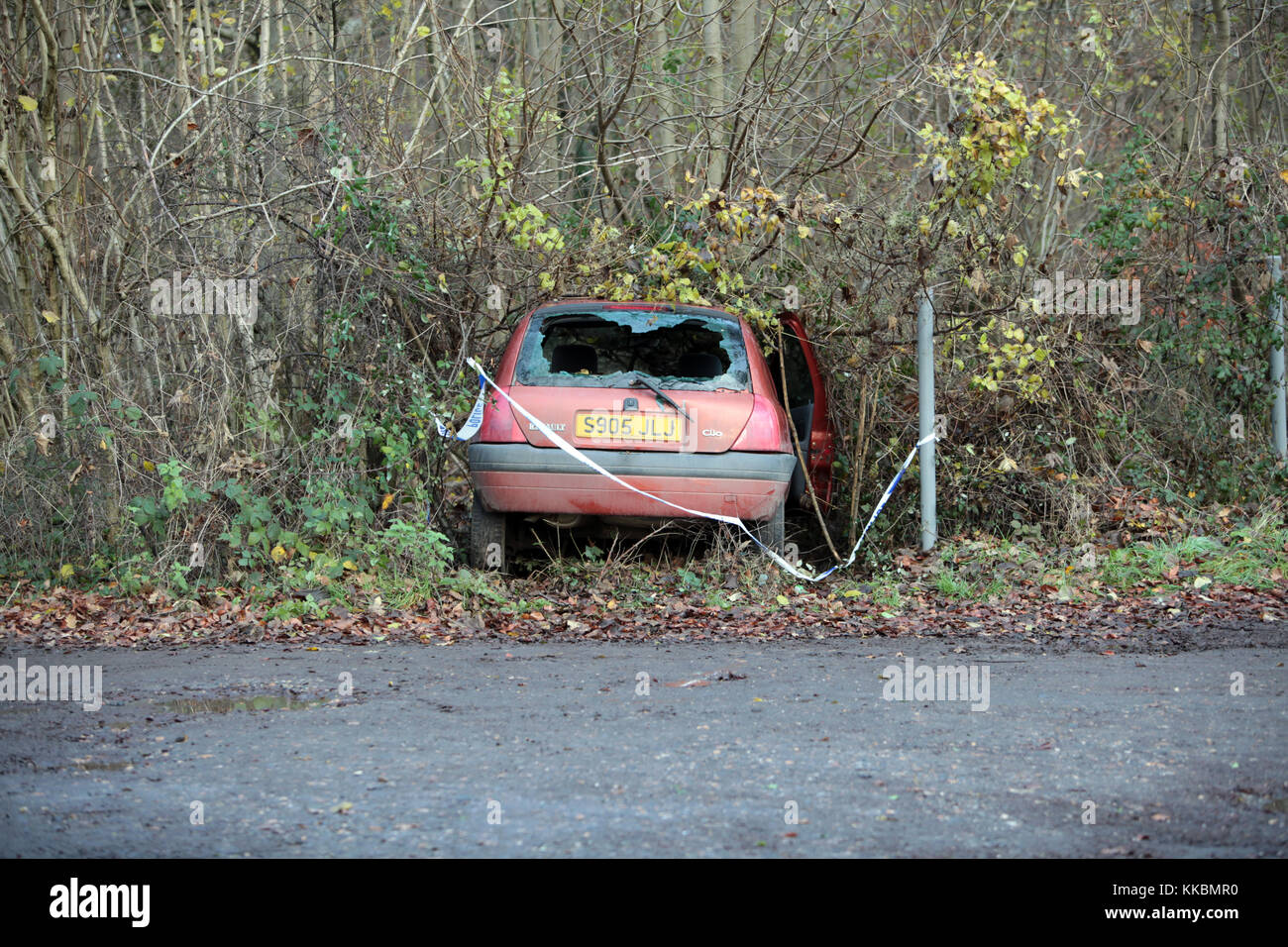 An abandoned car that crashed into a hedge on a rural road in Wiltshire England. Stock Photo