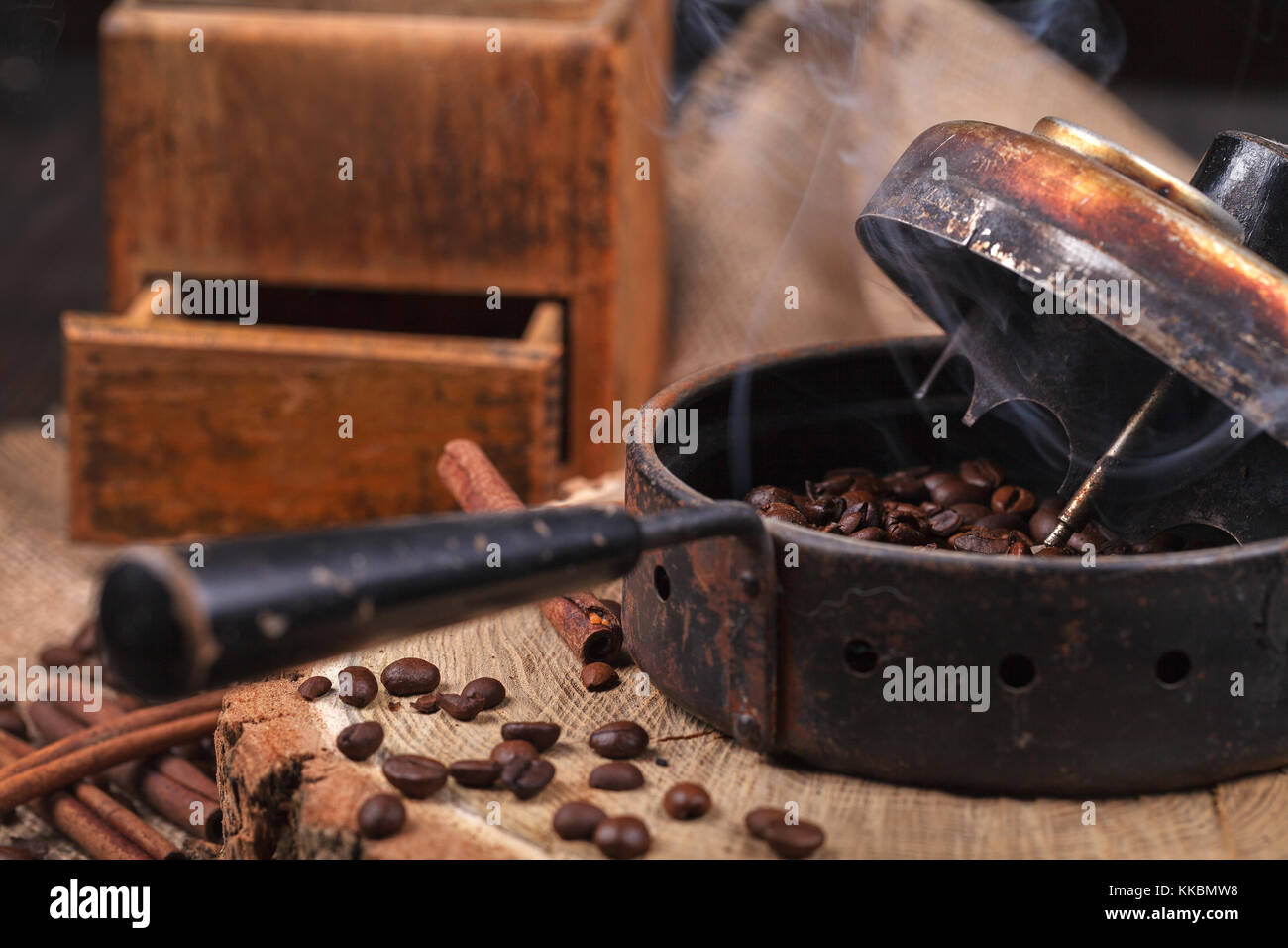 The device for roasting coffee beans, an old hand grinder. Smoky roast coffee on a wooden stand. Studio lighting. Stock Photo