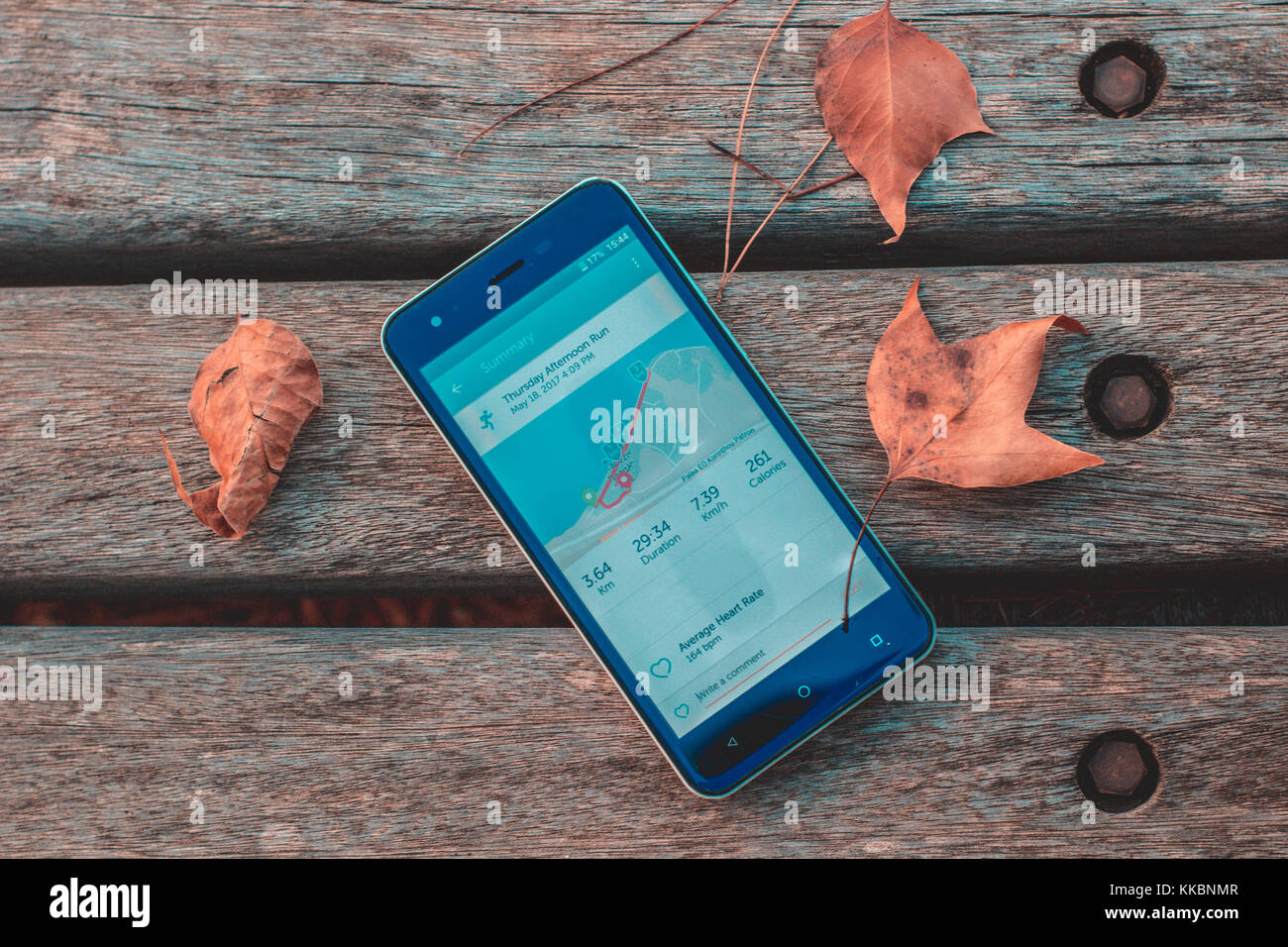 smartphone on a bench with a running app open showing stats after an autumn evening run with leaves on the side - Stock Image