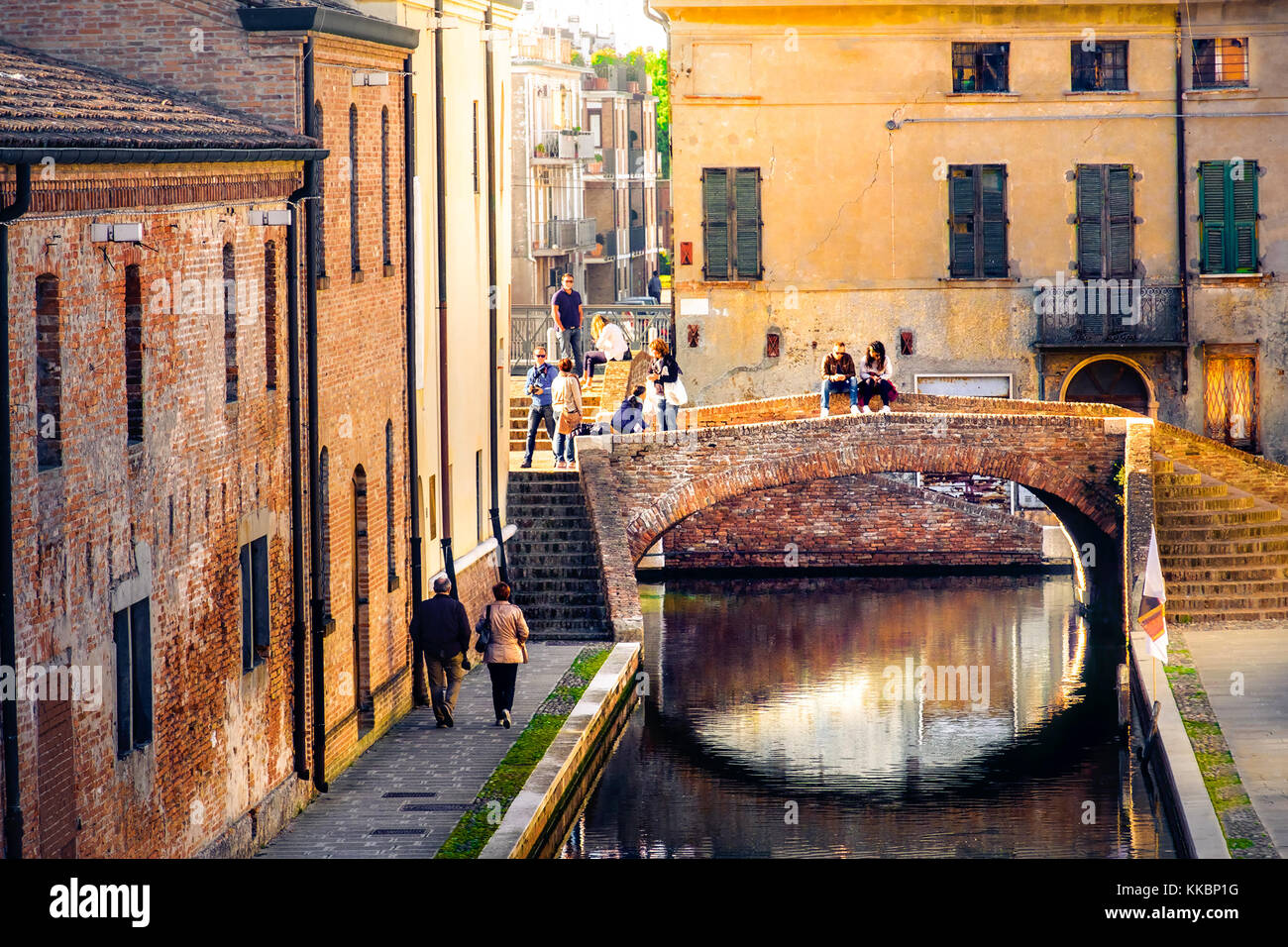 romantic getaways in italy,  warm tone lights at sunset over red bricks old buildings and bridge on the canal of - Stock Image