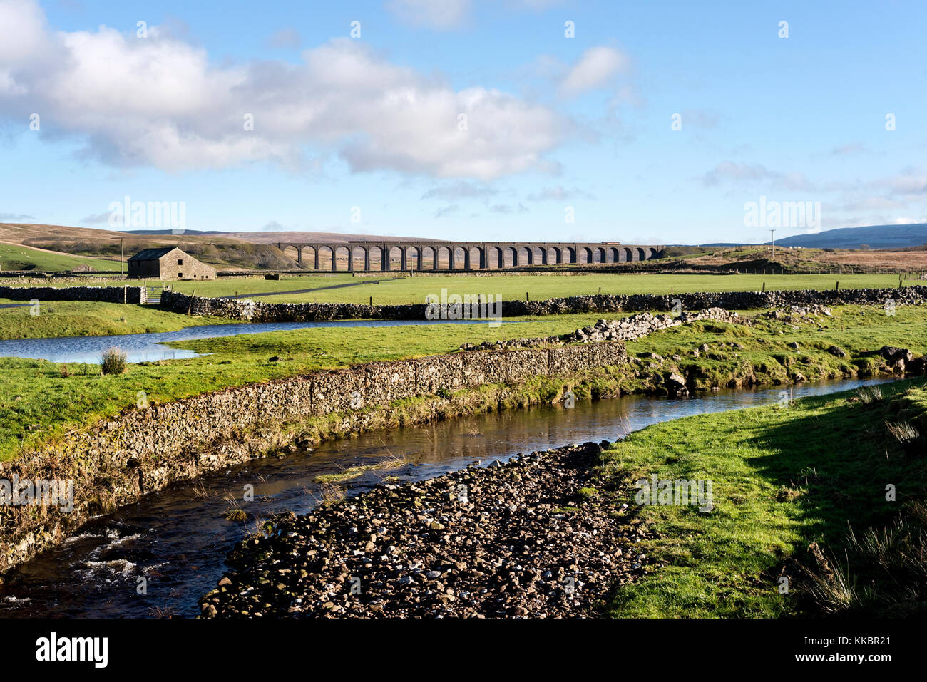 A minerals freight train crosses Ribblehead viaduct, Near Ingleton, North Yorkshire, in the Yorkshire Dales National - Stock Image