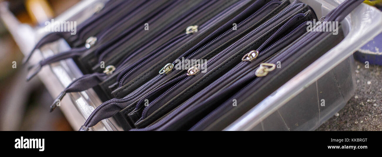 black wallets in plastic container Stock Photo