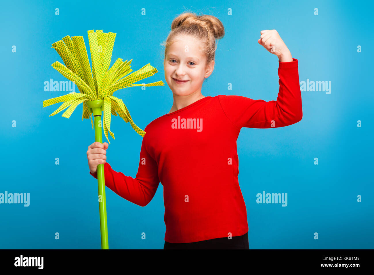 little fair-haired girl with a mop on blue background - Stock Image