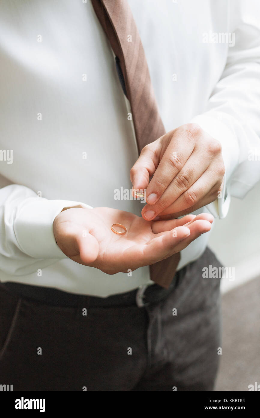 Man is taking off the wedding ring - Stock Image