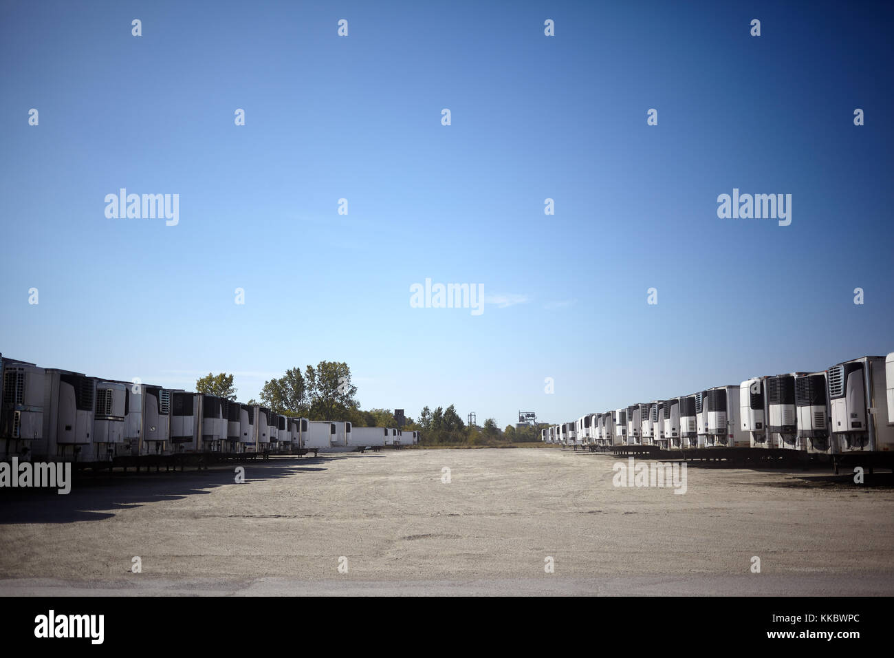 Vehicle park full of haulage trailers for freight parked in two long receding rows under a cloudless blue sky - Stock Image