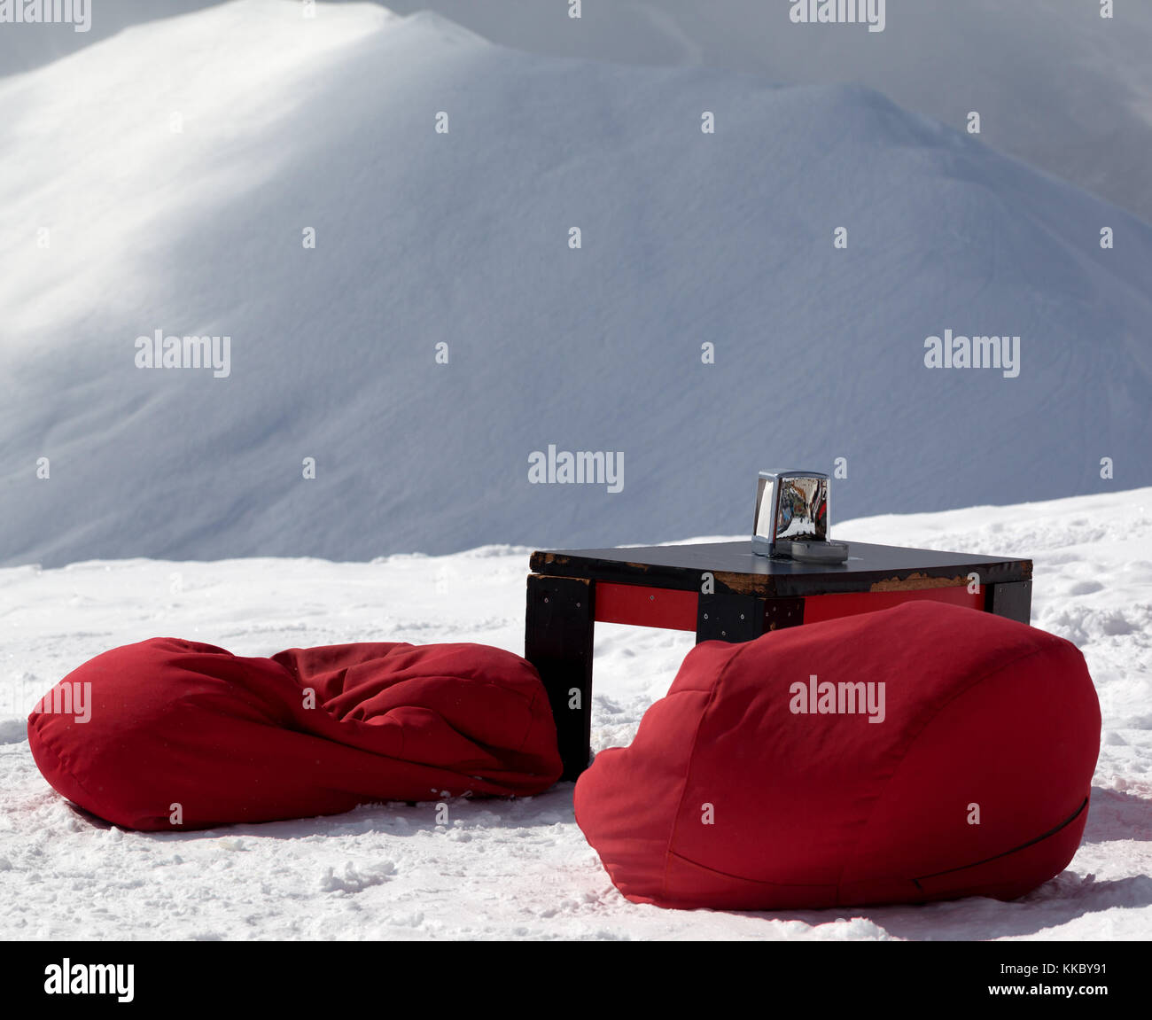 Red bean bag chairs and old table in outdoor cafe at ski resort and snowy slope for freeriding at background. Caucasus - Stock Image