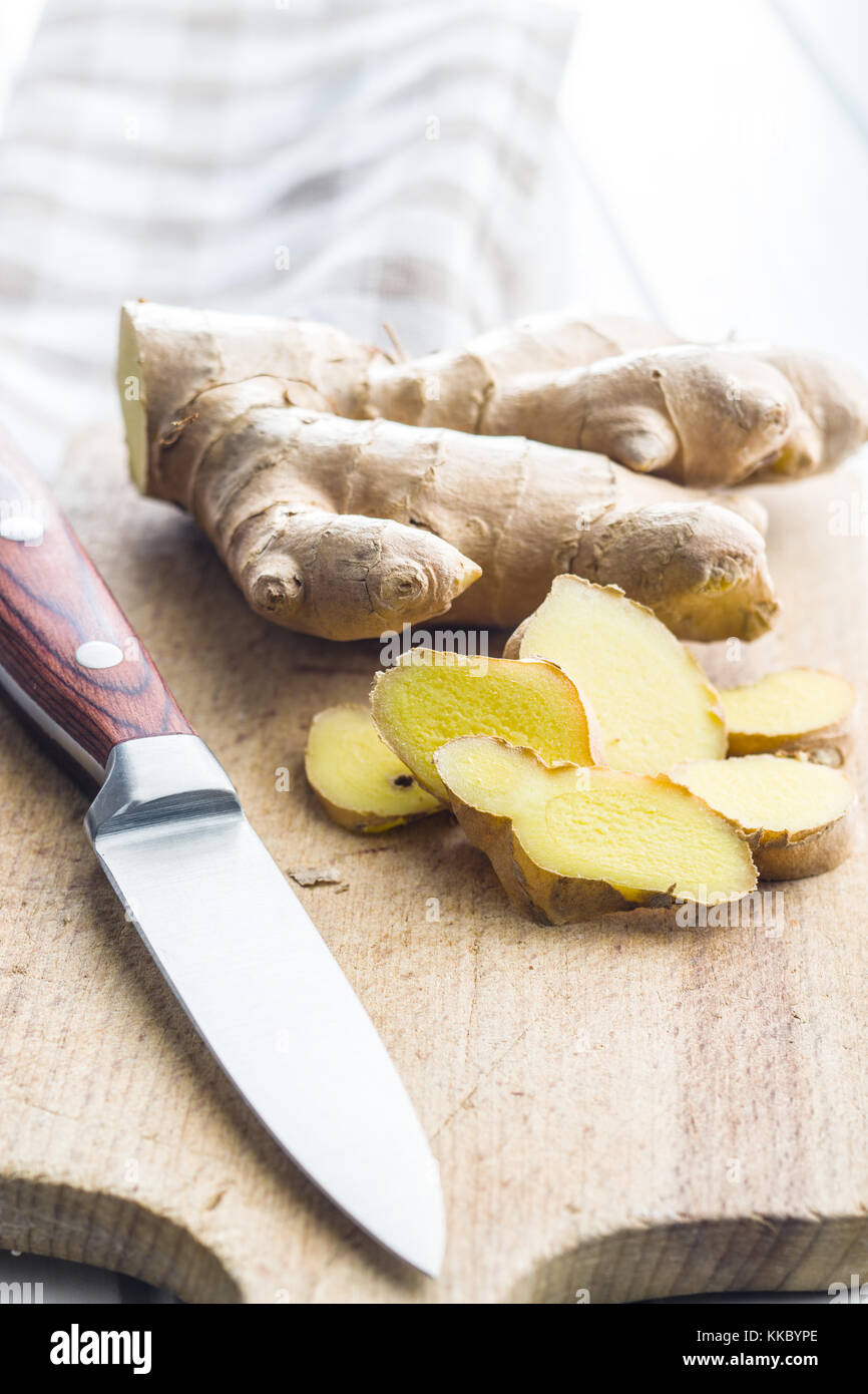 Sliced ginger root on cutting board. - Stock Image