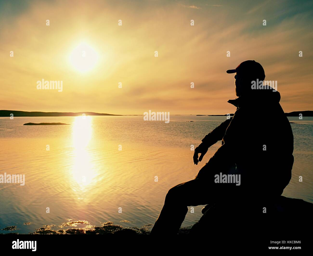 Silhouette of sitting man on stony coastline. Hiker seeing over siklent bay to evening sun - Stock Image