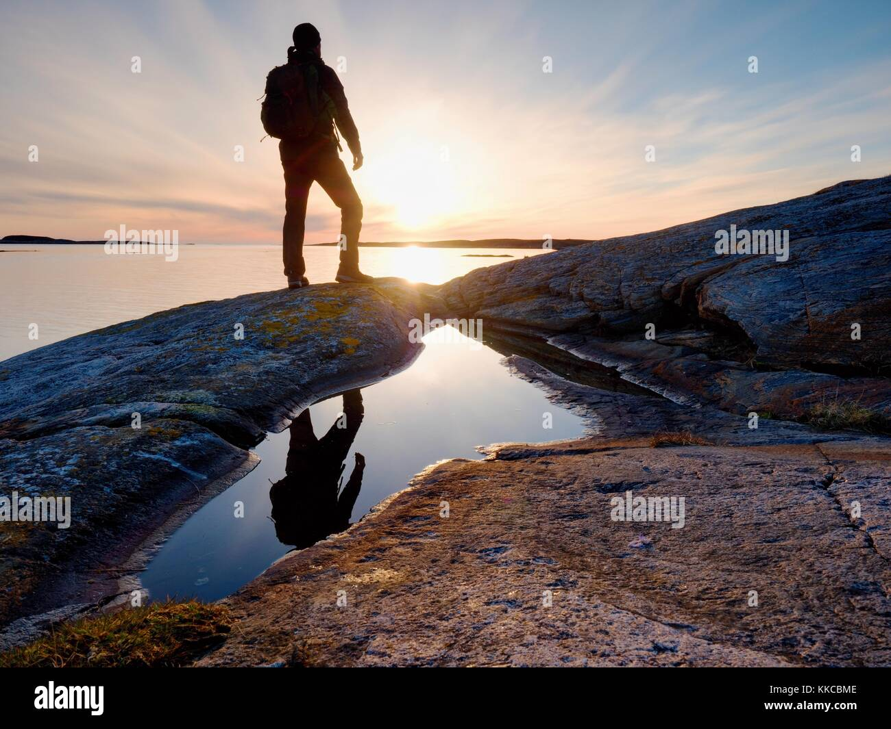 Tall backpacker watch clear sunny spring daybreak over sea. Hiker with backpack stand on rocky shore and his figure - Stock Image
