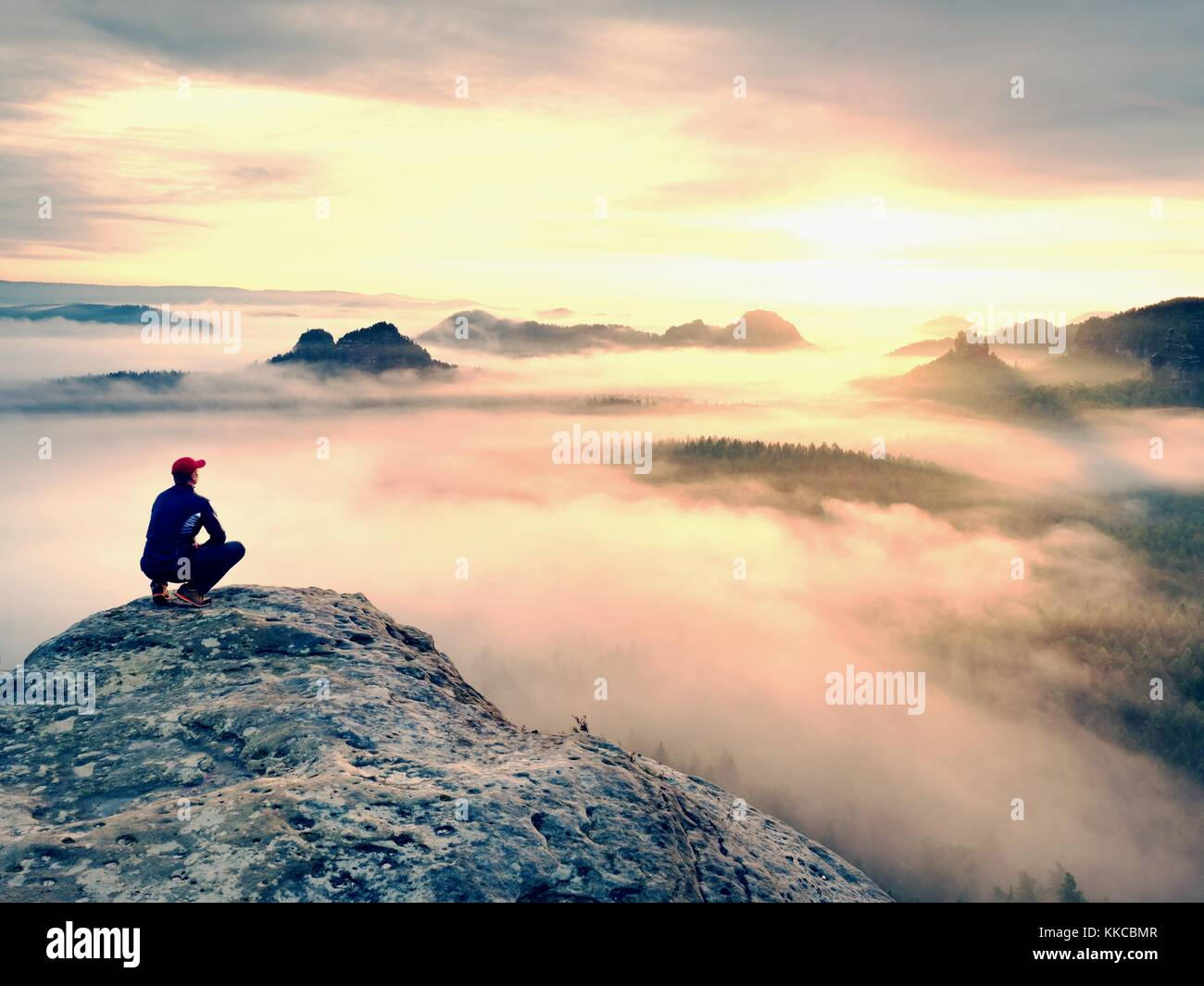 Moment of loneliness on exposed rocky summit. Man in black enjoy marvelous view. Hiker sit on the peak of rock and - Stock Image