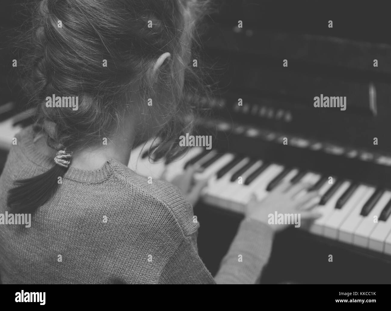 Little girl learning to play the piano. Black and white. - Stock Image
