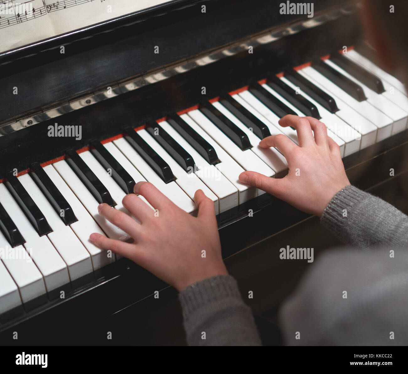 Child learns to play the piano. - Stock Image