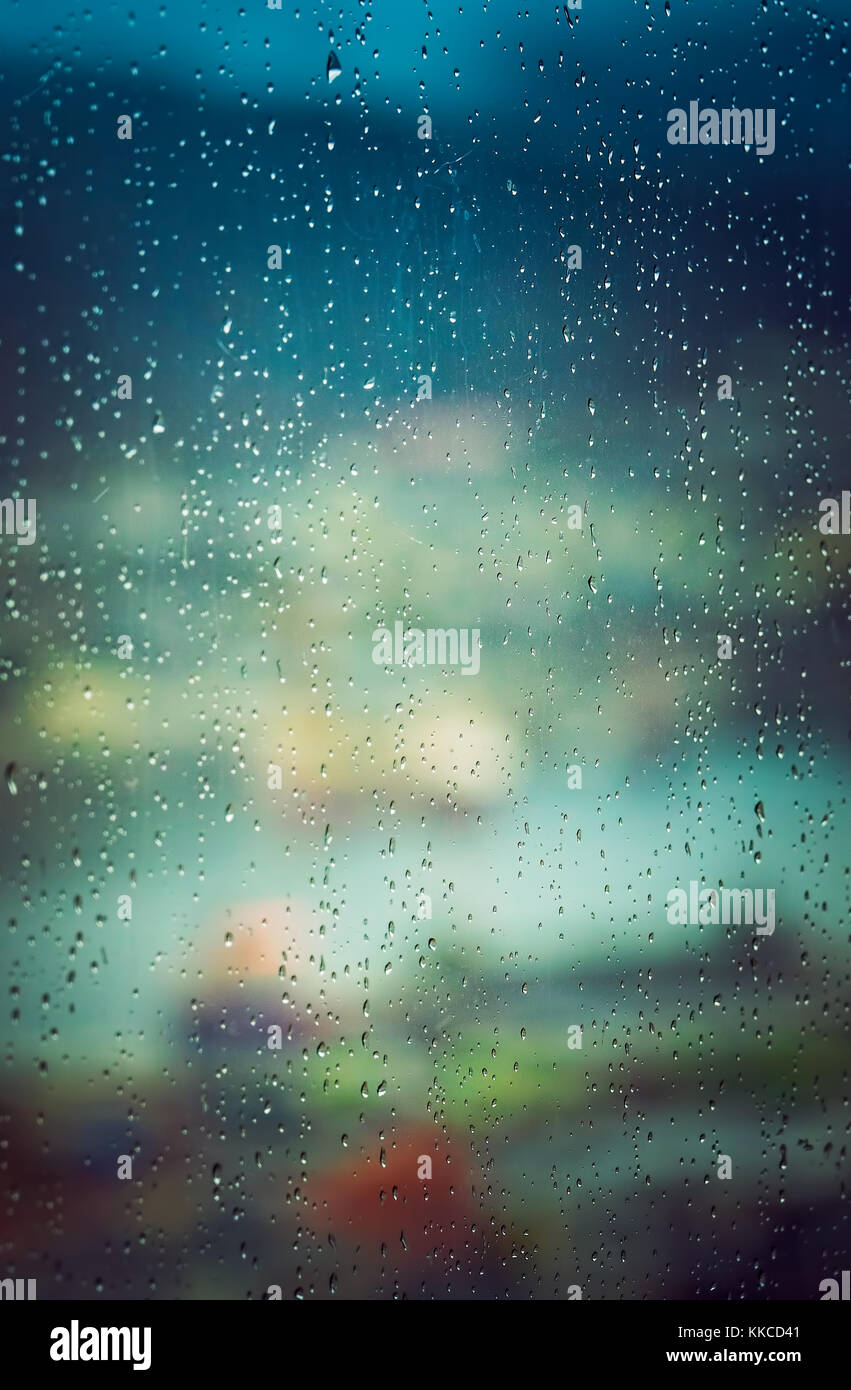 Defocused city colors through the wet window on a very rainy day - Stock Image
