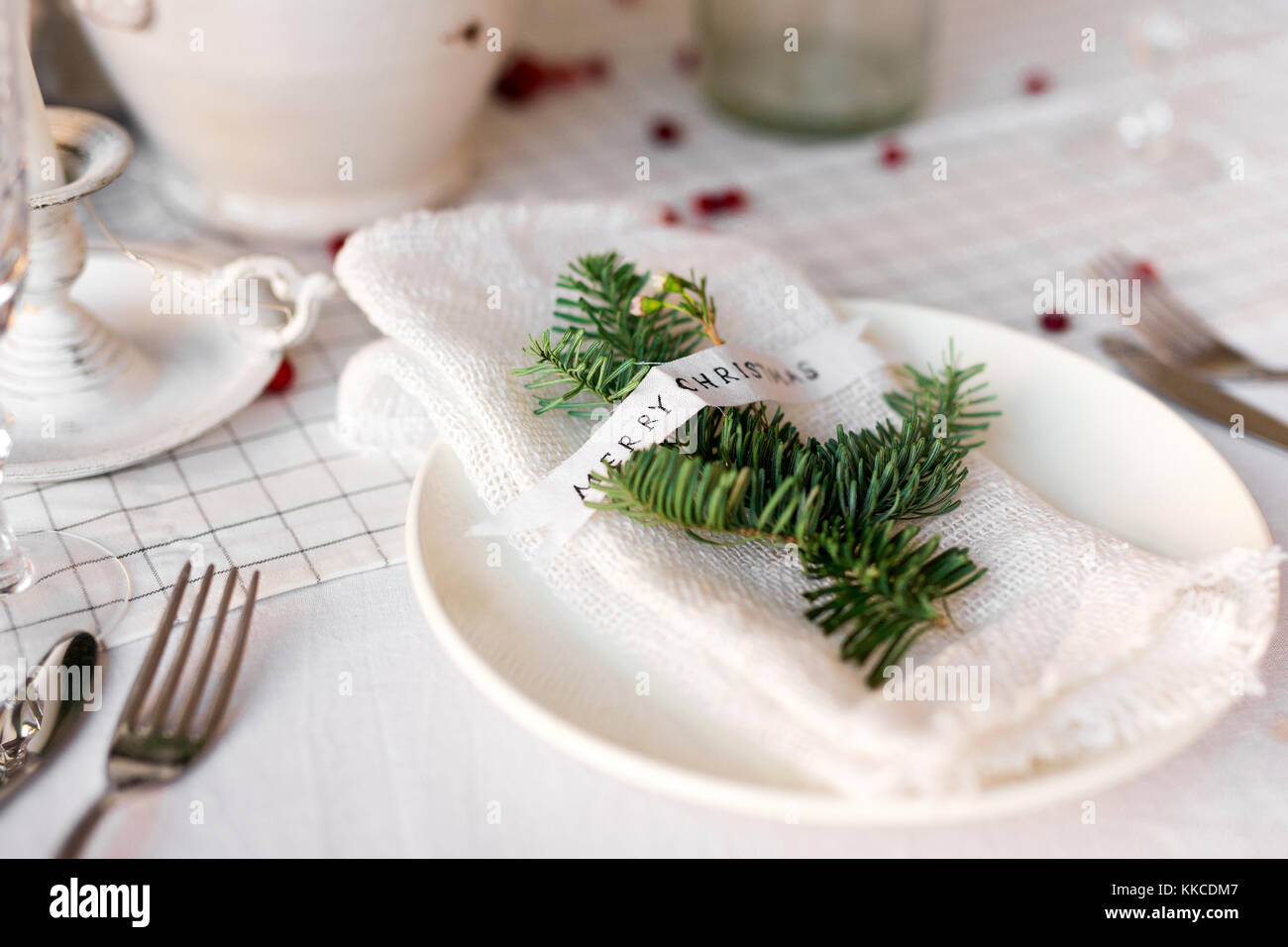 Christmas table: knife and fork, napkin and Christmas tree branch on a wooden table . New Year's decor of the - Stock Image