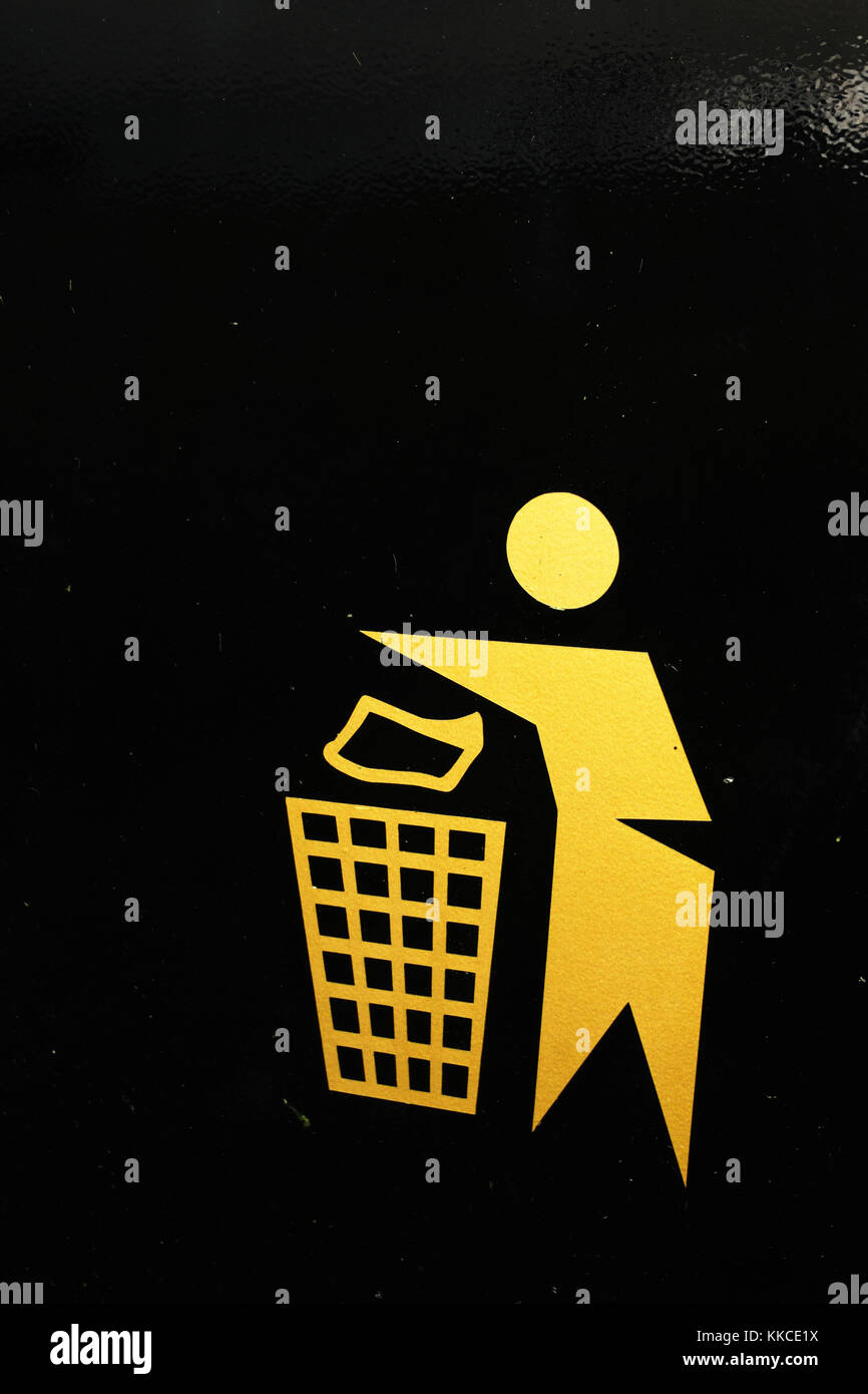 Stylised drawing of a person dropping rubbish in a litter bin, on the side of a public litter bin, Wales - Stock Image