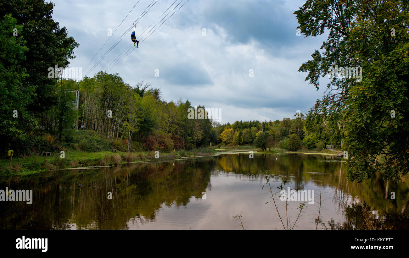 Man sliding on the longest over-water zipline in Ireland overlooking stunning woodland, two lakes and 17th-century - Stock Image
