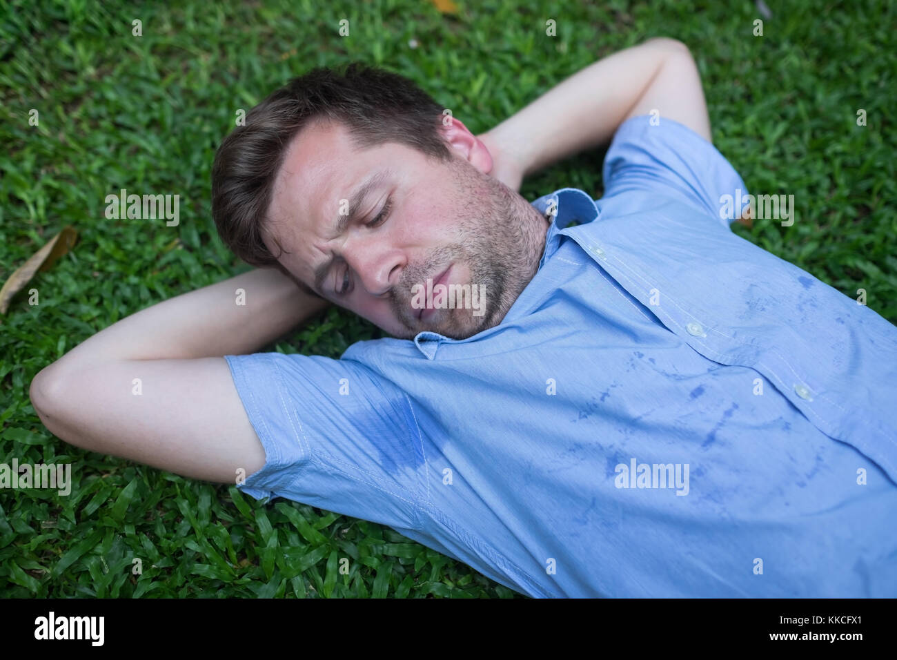 Caucasian, young man is resting on green grass and looking on his wet shirt. - Stock Image