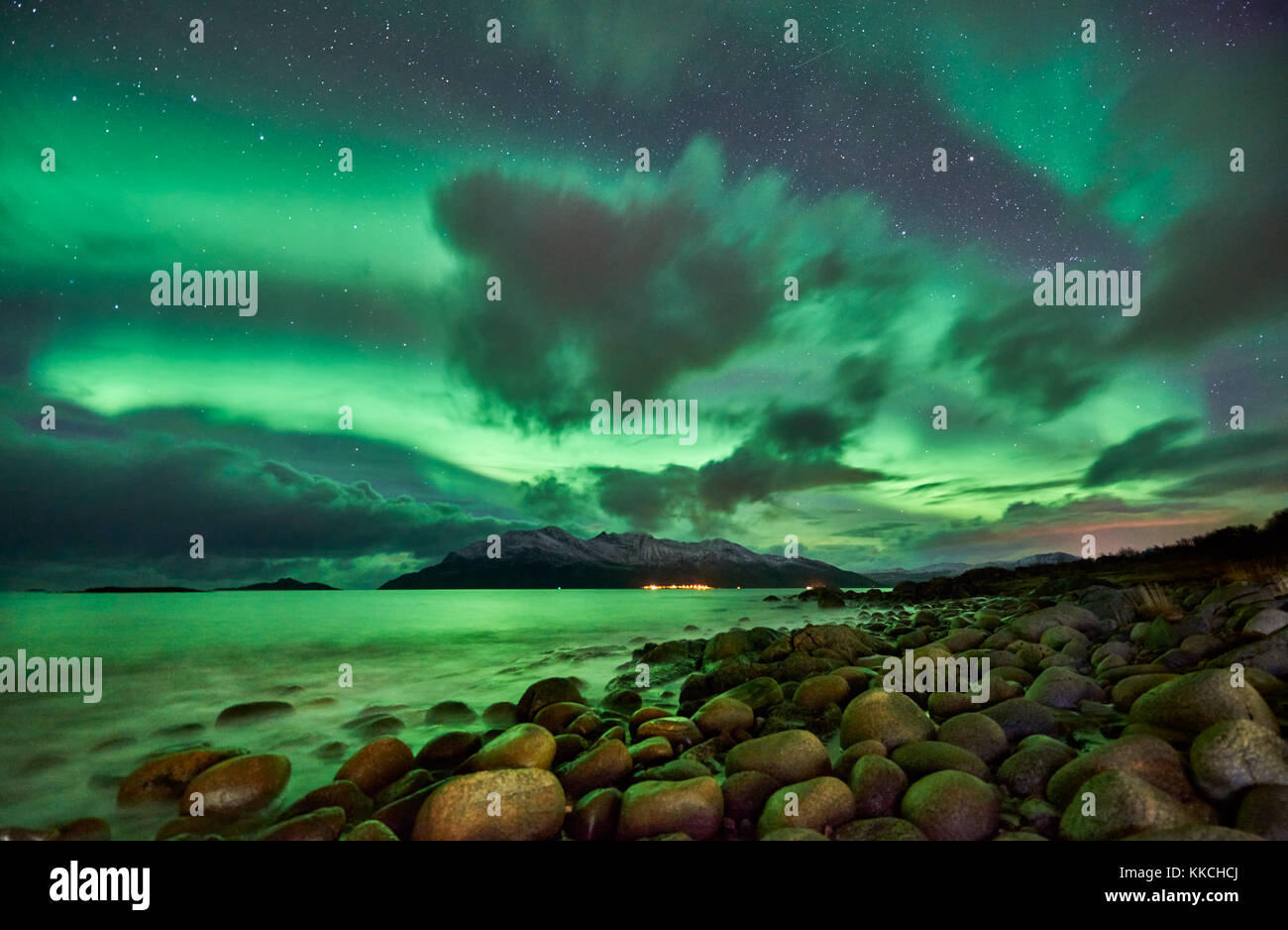 Aurora Borealis or northern lights over winter landscape in fjord of Kaldfjord, Tromvik, Tromso, Troms, Norway, - Stock Image