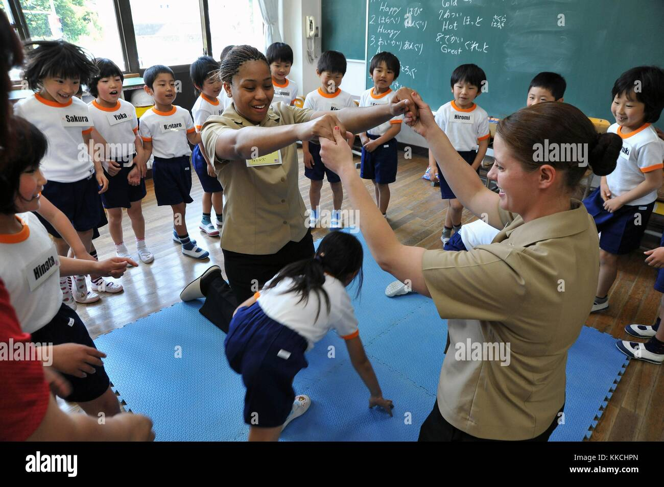 Hull Maintenance Technician 3rd Class Jane Clark and Boatswain's Mate Seaman Brittany Chiles, assigned to the Arleigh Burke-class guided-missile destroyer USS McCampbell DDG 85, play a game with Ogamo Elementary School first graders, Shimoda, Japan. Image courtesy Mass Communication Specialist Seaman Declan Barnes/US Navy. 2012. Stock Photo