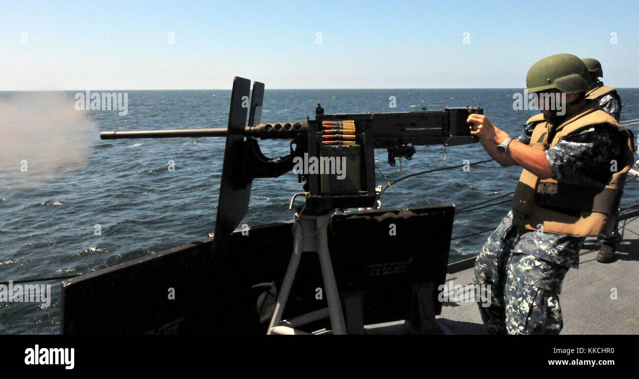 Electronics Technician 3rd Class Casey Colding fires the 50 caliber machine gun aboard the Oliver Hazard Perry-class Stock Photo