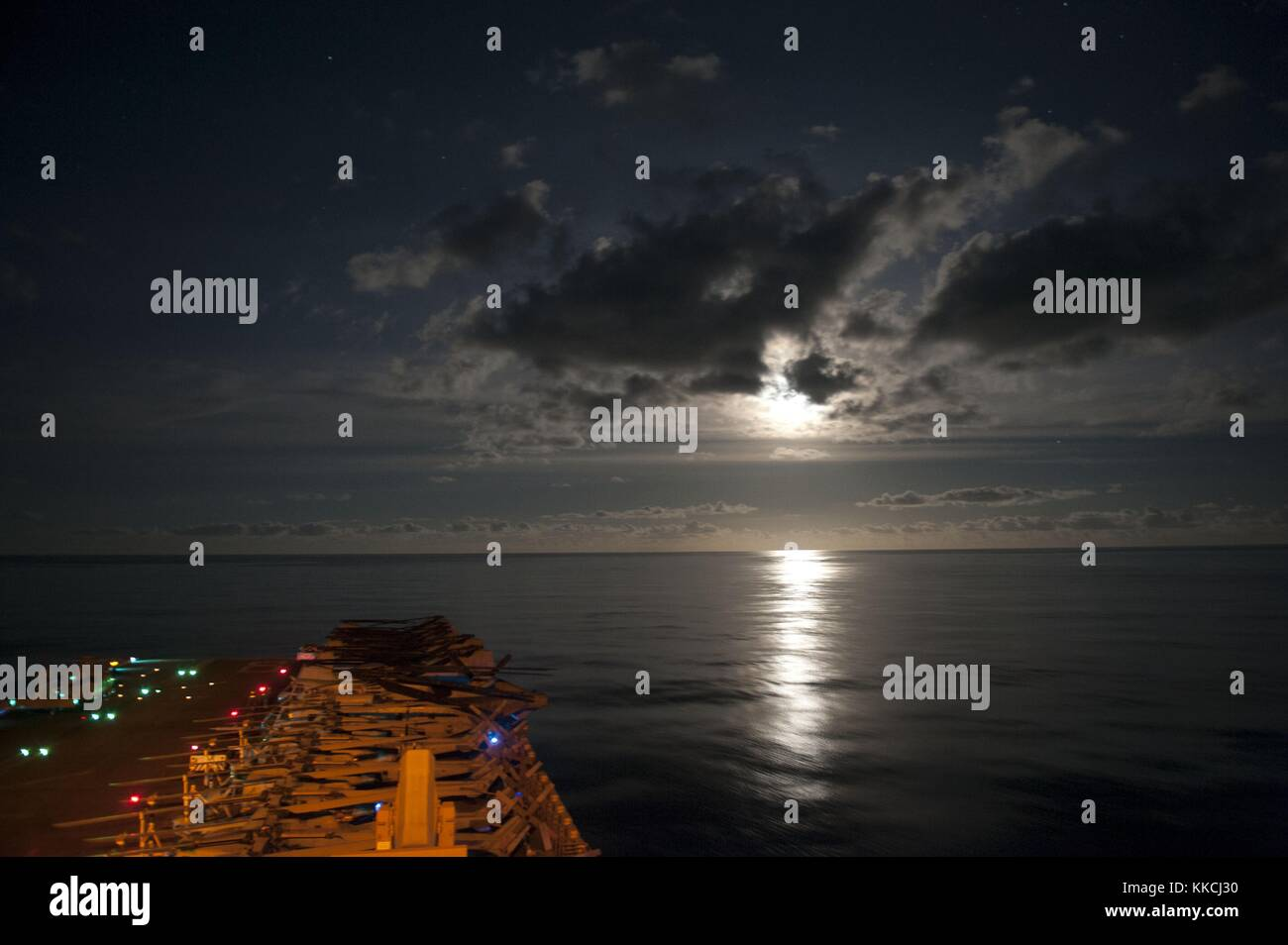 The amphibious assault ship USS Makin Island LHD 8 transits the Pacific Ocean under the light of a full moon, Pacific Stock Photo