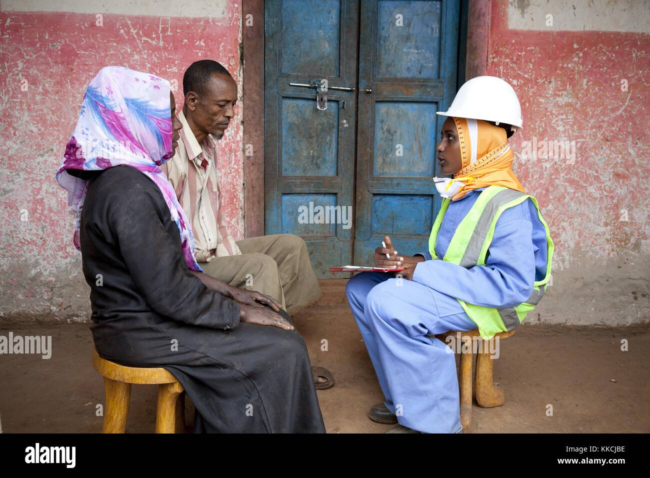 Mosquito eradication worker speaking with a family before spraying their house to prevent malaria. Courtesy Presidents' Stock Photo