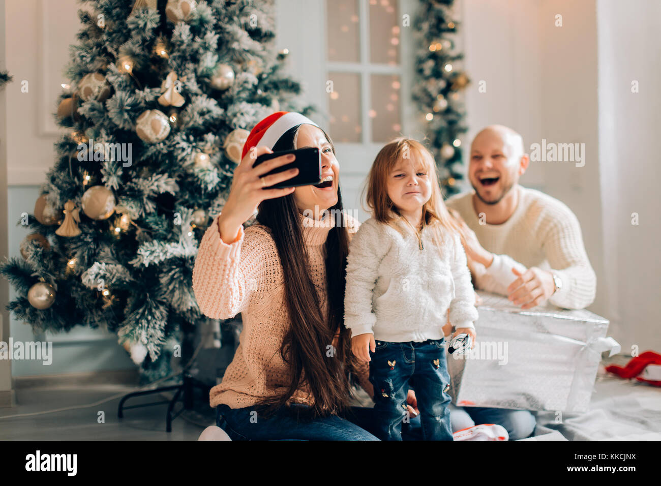 smiling mother, father and little girl making selfie with camera - Stock Image