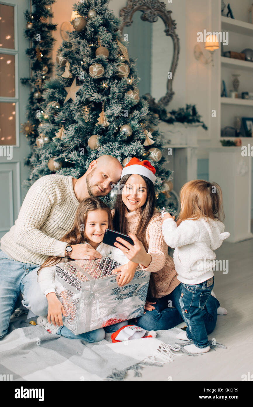 Cheerful family making comic xmas selfie and showing tongues - Stock Image