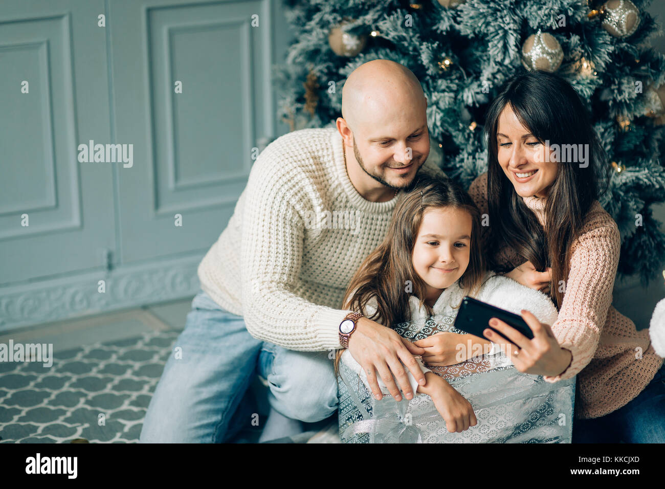 miling young family in Christmas atmosphere making photo with smartphone Stock Photo