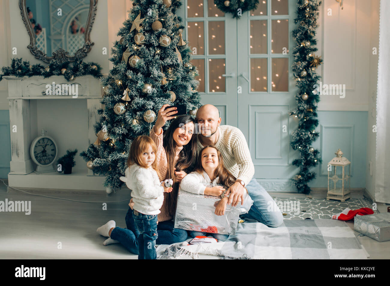 miling young family in Christmas atmosphere making photo with smartphone - Stock Image