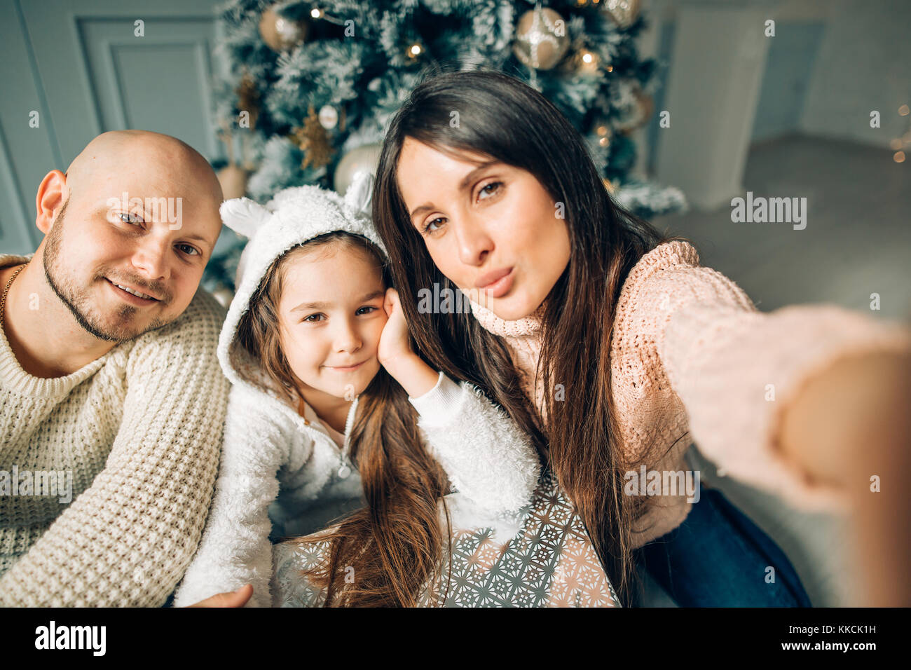 Young happy family of four taking a photo of themselves by a fireplace - Stock Image