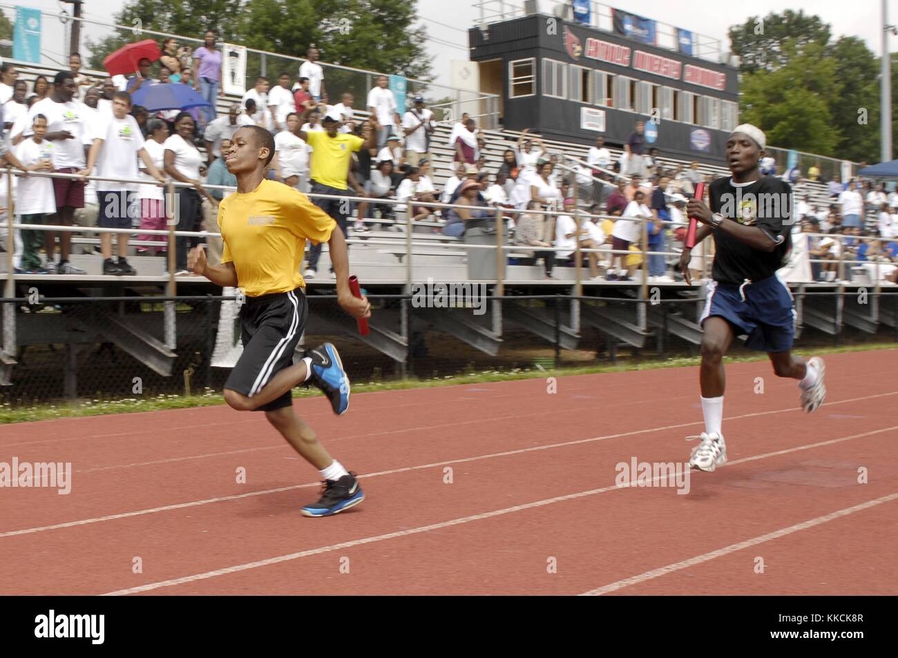 Runners at the 2012 Washington DC Special Olympics represent the US Navy and Army during a 4x100 meter relay race - Stock Image