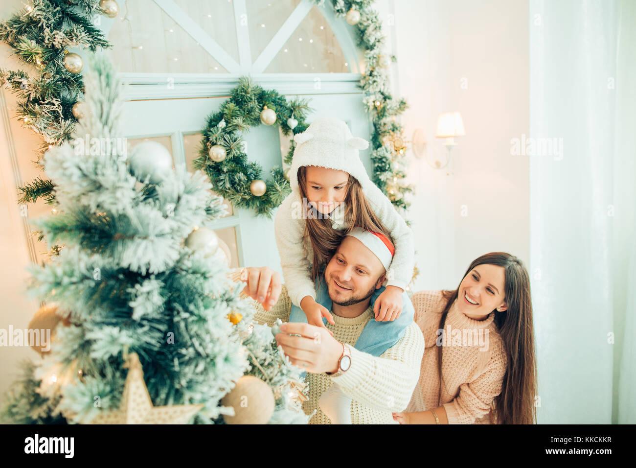 happy girl decorating Christmas tree.Family, christmas, ,happiness concept - Stock Image
